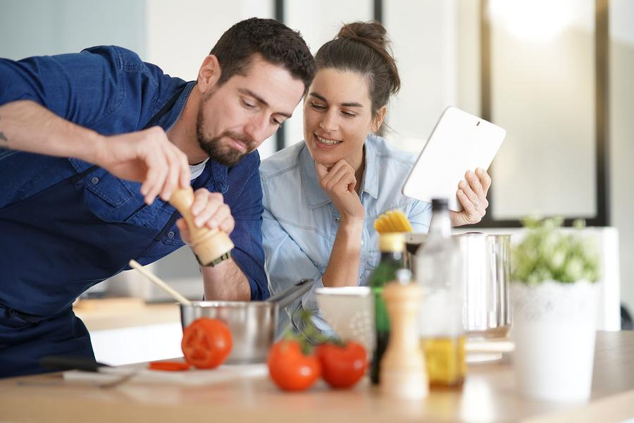Couple cooking in kitchen, reading recipe on tablet